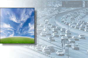 Blue sky with wispy clouds over a green horizon; heavy traffic on a freeway.